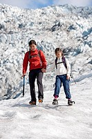 Mother and daughter walking on glacier