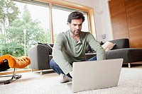 Germany, Bavaria, Nuremberg, Mature man using laptop in living room (thumbnail)
