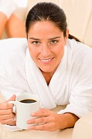 Attractive woman in white bathrobe hold coffee