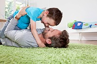 Germany, Berlin, Father and son having fun at home, smiling