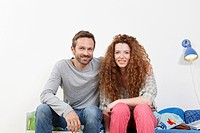 Germany, Berlin, Couple sitting on bed, smiling, portrait