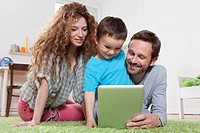Germany, Berlin, Family using digital tablet on floor (thumbnail)