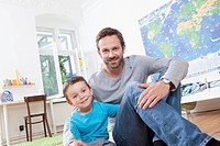 Germany, Berlin, Father and son sitting at home