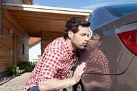 Germany, Bavaria, Nuremberg, Mature man kissing car
