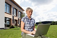 Germany, Bavaria, Nuremberg, Mature woman using laptop in garden (thumbnail)