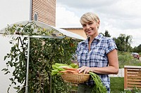 Germany, Bavaria, Nuremberg, Mature woman with vegetables in garden