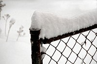 Snow piled high on a fence