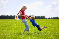 Germany, Bavaria, Boy and girl playing in meadow