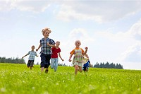 Germany, Bavaria, Group of children running through meadow