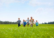 Germany, Bavaria, Group of children running through meadow (thumbnail)