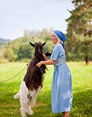 Germany, Bavaria, Mature woman playing with goat on farm