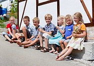 Germany, Bavaria, Group of children sitting in front of small house