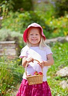 Germany, Bavaria, Girl with basket of strawberries in garden