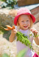 Germany, Bavaria, Girl picking carrots in garden