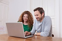 Germany, Berlin, Couple using laptop at home