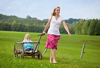 Germany, Bavaria, Mother pulling daughter in hand cart through meadow