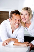 Germany, Mid adult couple in kitchen, smiling (thumbnail)