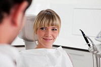 Germany, Young woman in dentist chair, smiling