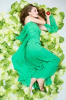 Young woman lying on salad (thumbnail)