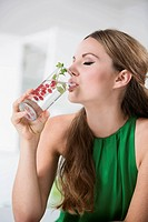 Germany, Young woman drinking water from glass with berries