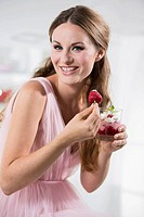 Germany, Young woman holding strawberry in her hand, smiling, portrait
