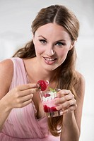 Germany, Young woman holding dipped strawberry in her hand, smiling, portrait