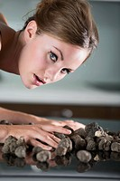 Germany, Young woman touching truffles, close up