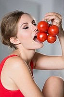 Germany, Young woman biting tomatoes, close up