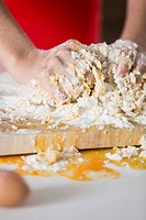 Germany, Young woman hands kneading batter