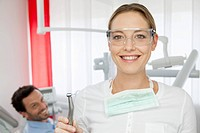 Germany, Dentist with safety glasses, patient in background
