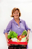 Senior woman with vegetable basket, smiling, portrait