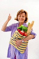 Senior woman with vegetable shopping bag and showing thumbs up, smiling, portrait (thumbnail)