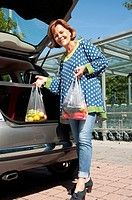 Germany, Munich, Senior woman stowing vegetable and fruit in car trunk