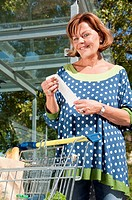 Germany, Munich, Senior woman holding supermarket receipt, smiling