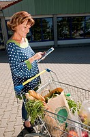 Germany, Munich, Senior woman using digital tablet with shopping cart