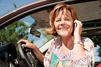 Germany, Munich, Senior woman siiting in car and talking on smart phone