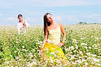Young lovely couple on a flower field