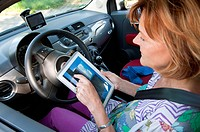 Germany, Munich, Senior woman sitting in car and using digital tablet