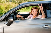 Germany, Munich, Senior woman sitting in car and showing victory sign