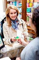 Woman buying medications in a pharmacy.