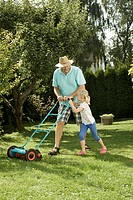Germany, Bavaria, Grandfather with children mowing lawn