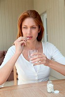 Woman taking pills to ease headache