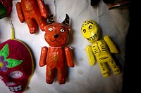 Paper mache dolls representing a red devil and a yellow skeleton sit for sale in a Mexican folk-art workshop in Mexico City, Mexico