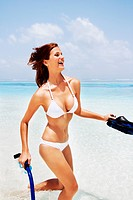 Excited young woman in bikini running into water with snorkelers and fins