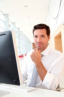 Salesman in front of desktop computer