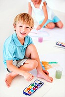 High angle portrait of a young boy painting watercolour pictures with his sister in the background
