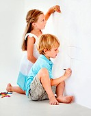 Two mischievous children drawing on the wall with crayons