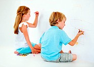 A brother and sister having a fun time drawing pictures with crayons on a wall