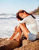 Attractive young woman sitting on a rock at the beach