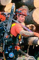 A woods worker in full safty gear walks by a log pile